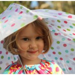 Four year old girl loving her polka dot umbrella